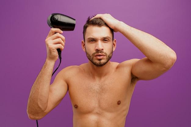 Europejczyk suszy włosy suszarką do włosów. skoncentrowany przystojny młody brodaty facet patrząc na kamery. na białym tle na fioletowym tle. sesja studyjna