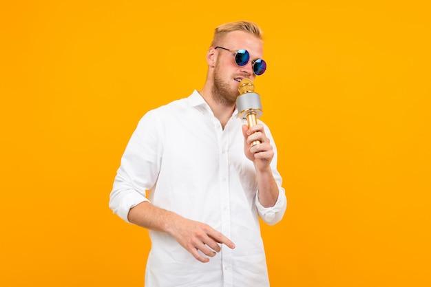 Europejczyk w białej koszuli z mikrofonem na żółto