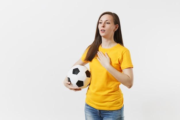 Europejka, fanka piłki nożnej w żółtym mundurze trzymająca piłkę nożną, śpiewająca hymn kraju na białym tle. sport, grać w piłkę nożną, kibicować, kibice wspierają ludzi, koncepcja stylu życia.