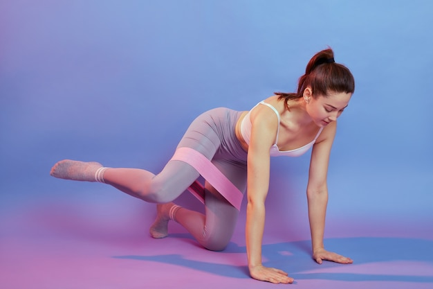 Europejka na czworakach z opaską na kolanach, trzymająca nogę na boku, kobieta ćwiczy w pomieszczeniu na białym tle na kolorowym tle, spogląda w dół, nosi stylową odzież sportową.