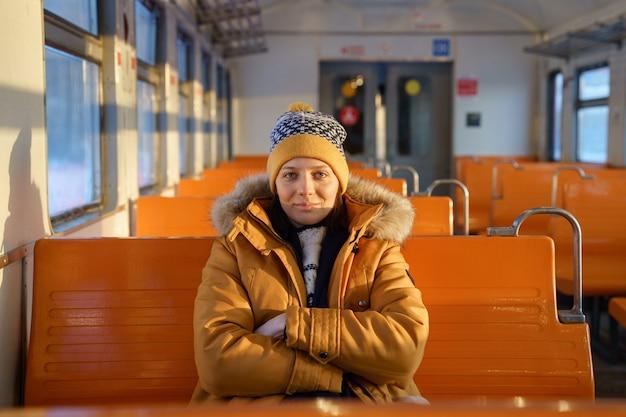 Europejka nosi kapelusz podróżując lokalnym pociągiem w okresie zimowym, skrzyżowane ręce, patrząc na kamery.
