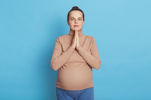 Europejka piękna kobieta w ciąży z dłońmi razem modląca się o swoje przyszłe dziecko ubrane w swobodny strój, stoi odizolowana na niebieskiej ścianie, próbuje się zrelaksować przed pójściem do domu położniczego.