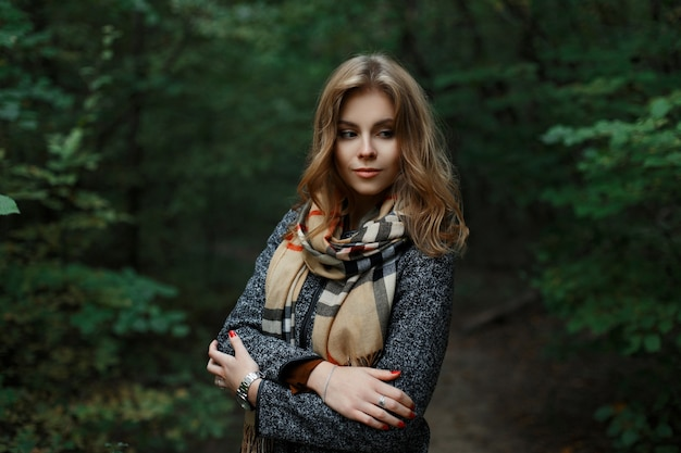 Europejka słodka młoda kobieta o blond włosach w luksusowym szarym płaszczu z szalikiem w kratkę pozuje w parku w pobliżu zielonych drzew