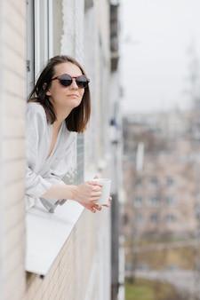 Europejka w okularach przeciwsłonecznych z kubkiem kawy lub herbaty wygląda przez okno i uśmiecha się