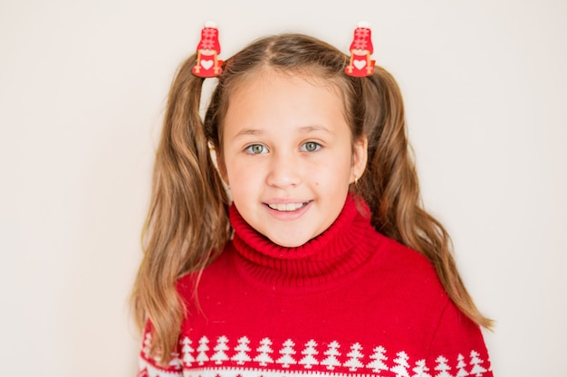 Europejka w świątecznym swetrze ze świątecznymi ozdobami na jej kucykach