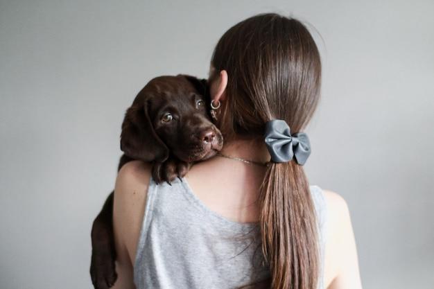Europejka w szarych ubraniach trzyma przed sobą szczeniaka labrador retrievera w kolorze czekolady