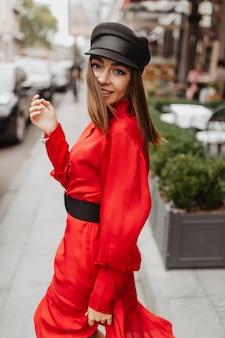 Europejska atrakcyjna dziewczyna. ciemnooka brunetka z krótkimi włosami pozuje do portretu ulicy