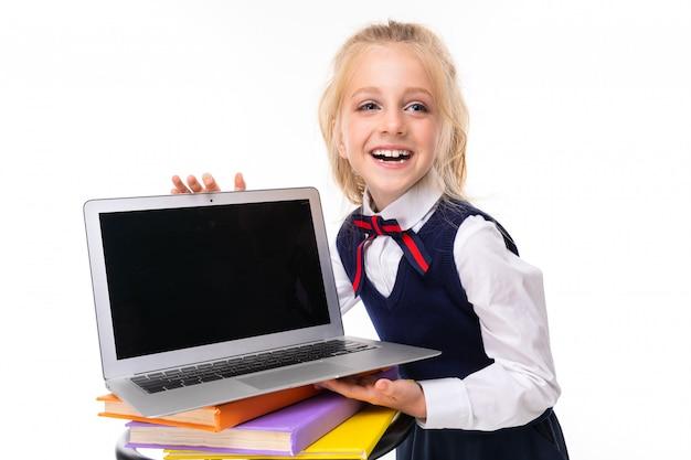 Europejska blondynki dziewczyna trzyma laptop z mockup na biel ścianie