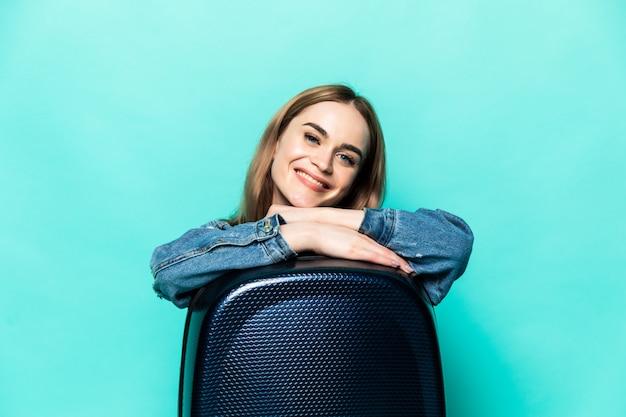 Europejska caucaian fwoman ubrana w letnie ubrania siedzi przy walizce z biletami samolotowymi marząc o locie i podróży, na białym tle na zielonej ścianie