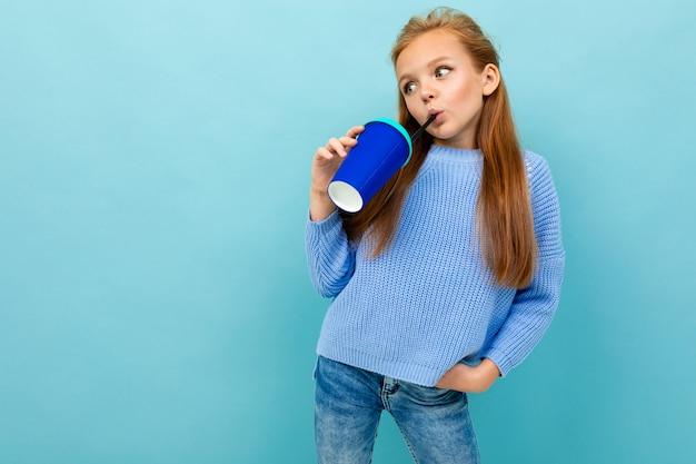 Europejska dziewczyna pije coś ze szkła na jasnoniebieskiej ścianie z copyspace