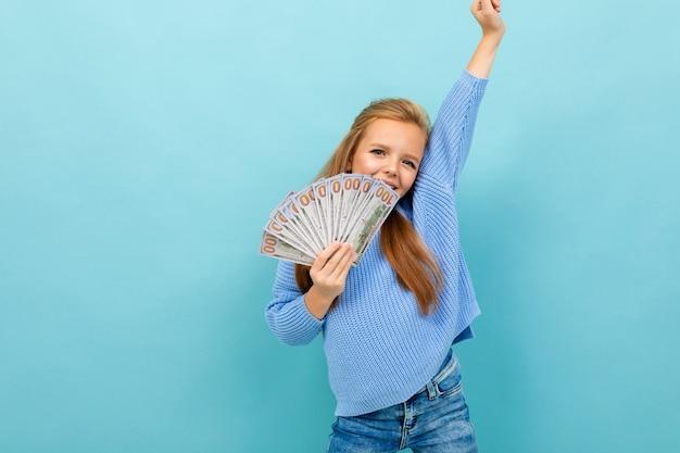 Europejska dziewczyna trzyma pieniądze w ręce na jasnoniebieskiej ścianie