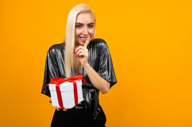 Europejska dziewczyna trzyma pudełko z prezentem i mówi sekret na odosobnionym żółtym tle z miejscem na kopię