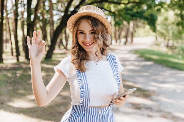 Europejska dziewczyna w kapeluszu pozowanie w parku z wyrazem zadowolonej twarzy i macha ręką. radosna modelka w stroju vintage lato zabawy.