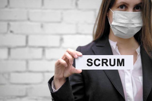 Europejska dziewczyna w masce medycznej trzyma znak z napisem scrum