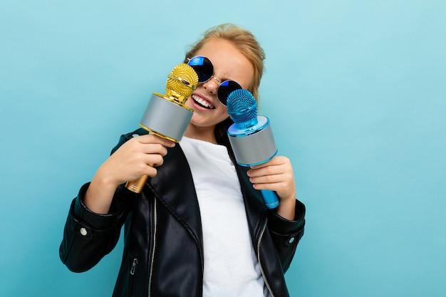 Europejska dziewczyna w okularach przeciwsłonecznych z dwoma mikrofonami w ręku na jasnoniebieskiej ścianie
