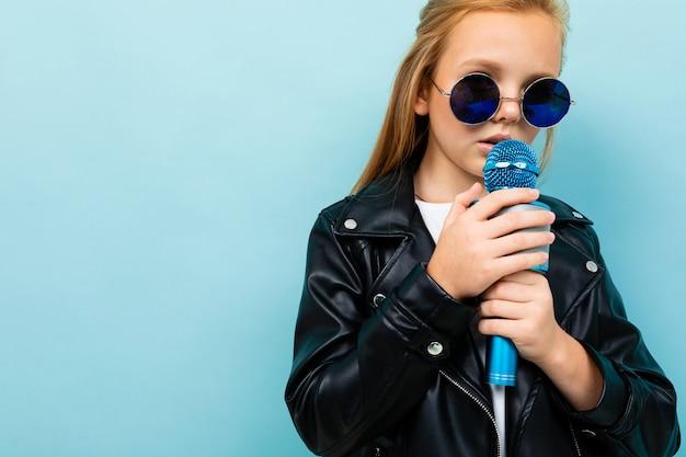Europejska dziewczyna w skórzanej kurtce w okularach przeciwsłonecznych śpiewa z mikrofonem na jasnoniebieskim