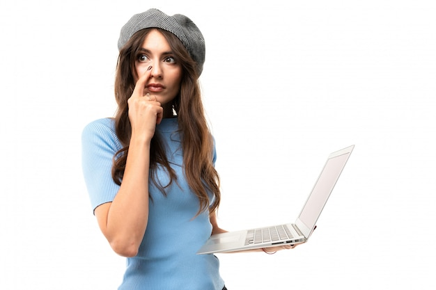 Europejska dziewczyna z laptopem w rękach na białej ścianie