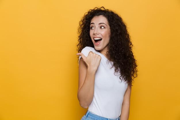 Europejska kobieta 20-latka z kręconymi włosami wskazująca palcem na bok na copyspace na żółto