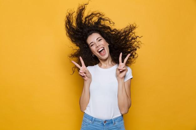 Europejska kobieta 20s śmiejąca się i bawiąca się z trzęsącymi się włosami na żółto