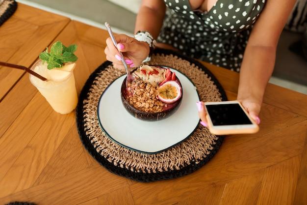 Europejska kobieta przy użyciu telefonu komórkowego w kawiarni.