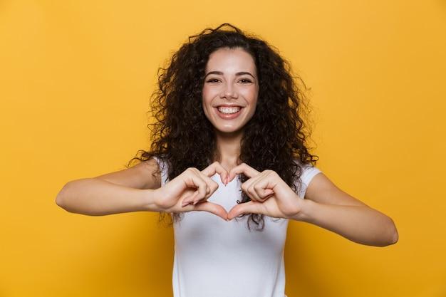 Europejska kobieta w wieku 20 lat z kręconymi włosami uśmiechnięta i pokazująca kształt serca z palcami izolowanymi na żółto