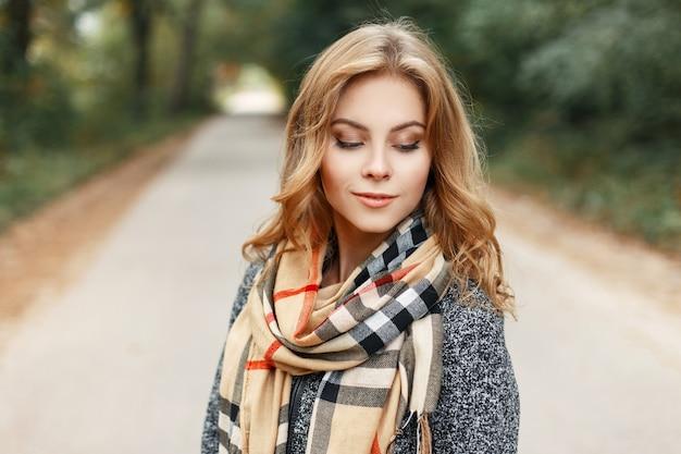 Europejska ładna młoda kobieta o blond włosach w szarym, stylowym płaszczu z beżowym szalikiem w kratkę, ciesząca się weekendem w parku z zielonymi drzewami