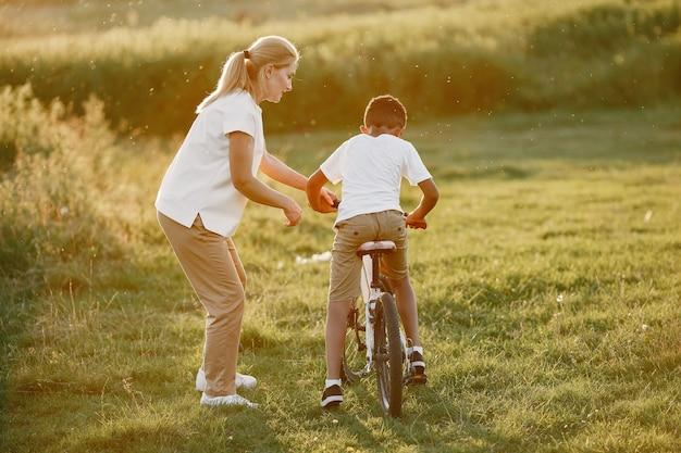 Europejska matka i afrykański syn. rodzina w letnim parku. dziecko z rowerem.