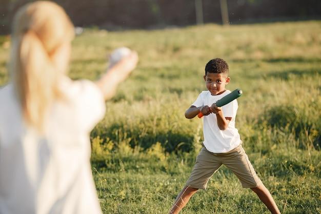 Europejska matka i afrykański syn. rodzina w letnim parku. ludzie bawią się gryzieniem i piłką.
