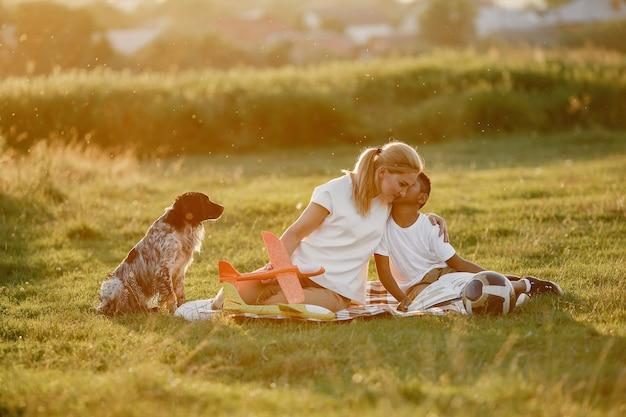 Europejska matka i afrykański syn. rodzina w letnim parku. ludzie siedzący na kocu.