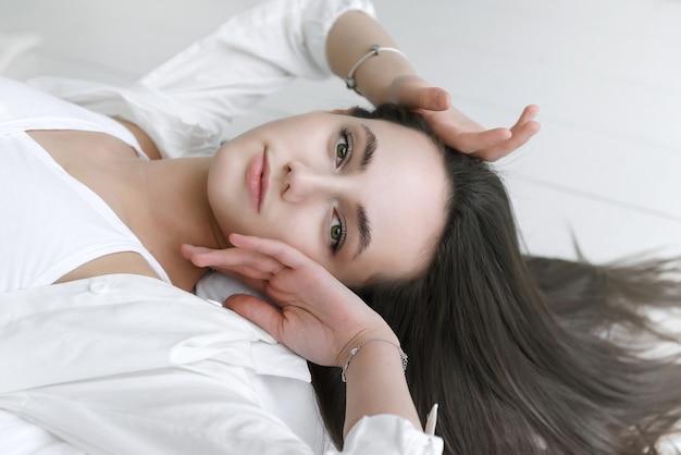 Europejska młoda brunetka kobieta w białej koszuli
