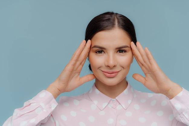 Europejska młoda kobieta dotyka głowy