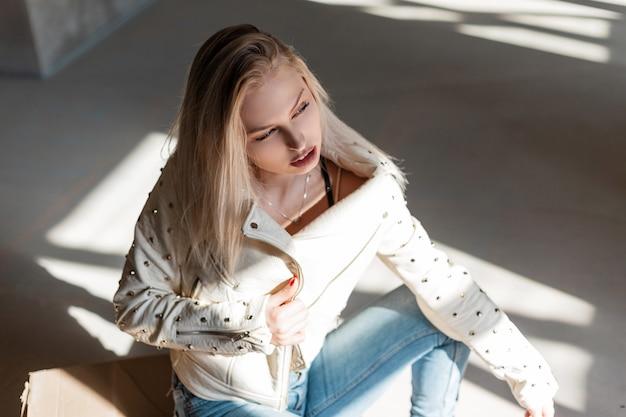 Europejska młoda kobieta w vintage skórzanej kurtce w modnych zgranych dżinsach w niebieskich modnych kowbojskich butach, pozowanie, siedząc w pomieszczeniu z promieniami słonecznymi