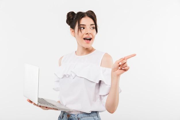 Europejska młoda kobieta z fryzurą double buns i szelki dentystyczne wskazując palcem na bok, trzymając laptopa, na białym tle