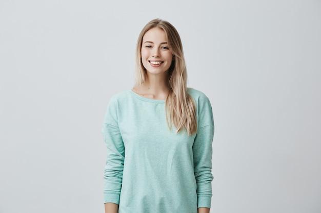 Europejska modelka z długimi blond włosami, nosi jasnoniebieski sweter