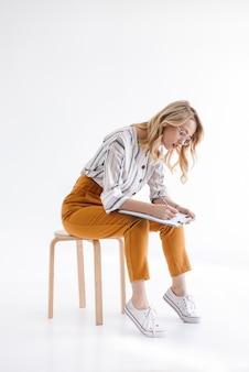Europejska myśląca kobieta w okularach siedzi na krześle i pisze w schowku na białym tle nad białą ścianą