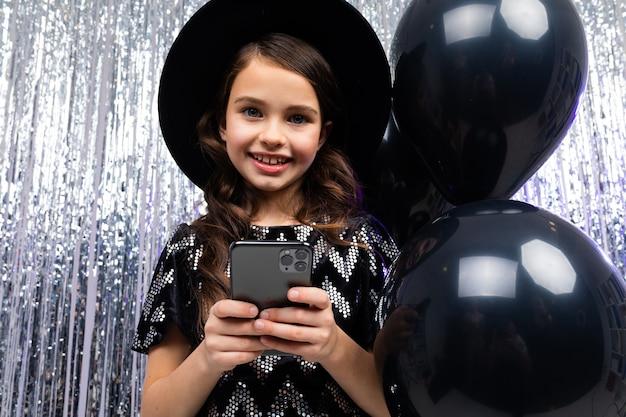 Europejska nastolatka z telefonem w jej urodziny na tle czarnych balonów z helem i świecidełka.
