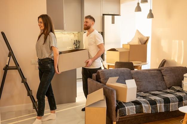 Europejska para niosąca karton z rzeczami w domu. koncepcja przeprowadzki do nowego mieszkania. idea młodej rodziny. piękna dziewczyna i brodaty mężczyzna. wnętrze apartamentu typu studio. słoneczny dzień