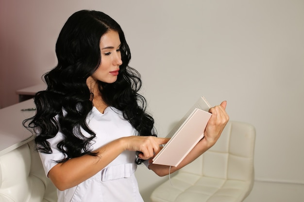 Europejska piękna dziewczyna w białym mundurze ubrania stoi w białym nowoczesnym wnętrzu.
