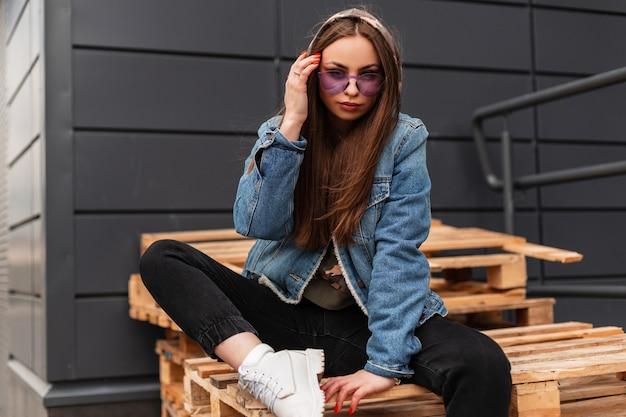 Europejska piękna młoda hipster kobieta w modnych fioletowych okularach w stylowej kurtce dżinsowej w czarnych dżinsach pozowanie siedząc na starych drewnianych paletach w mieście. atrakcyjna dziewczyna n modna odzież na zewnątrz