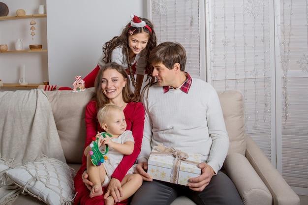 Europejska rodzina siedzi na kanapie z prezentami świątecznymi