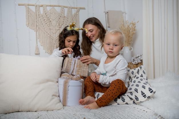 Europejska rodzina siedzi na łóżku z prezentami