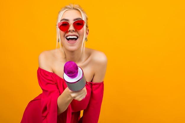 Europejska seksowna dziewczyna prowadząca imprezę w czerwonej sukience z odkrytymi ramionami z mikrofonem w dłoniach
