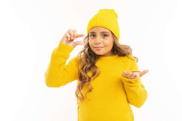 Europejska śliczna dziewczyna w żółtych ubraniach pokazuje coś małego z rękami z egzaminem próbnym up na bielu z copyspace