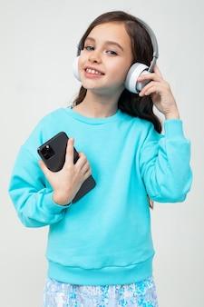 Europejska śliczna młoda dziewczyna w niebieskiej bluzce relaksuje się przy muzyce w dużych stylowych słuchawkach z telefonem w dłoniach na białym tle studio.