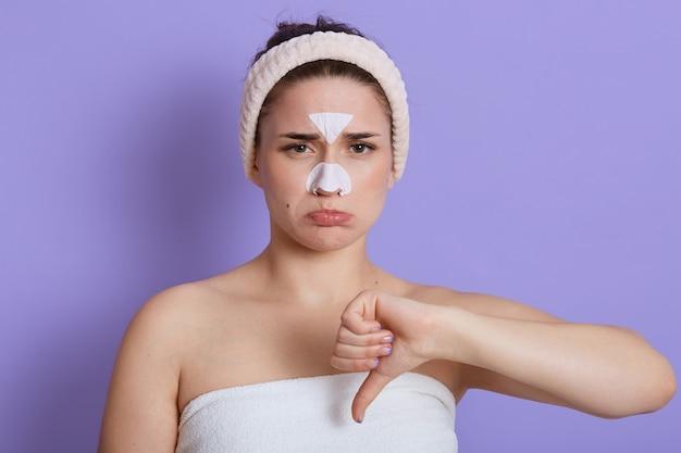 Europejska smutna piękna kobieta z opaską na włosy i maską na nosie i czole odizolowaną na liliowej ścianie, mająca zły nastrój, wydymająca usta i marszcząca brwi, pokazująca kciuk w dół.