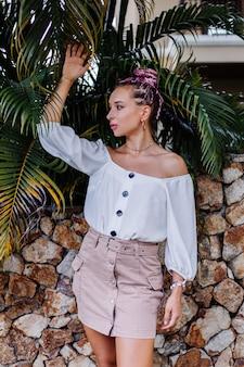 Europejska stylowa kobieta z różowymi kolorowymi letnimi warkoczami w beżowej spódnicy i białej bluzce