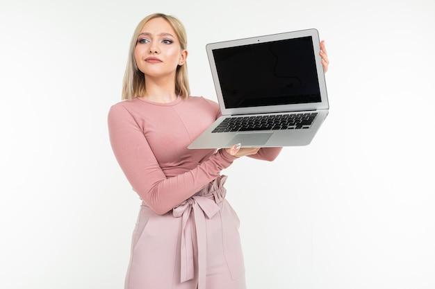 Europejska stylowa młoda kobieta pokazuje wyświetlacz laptopa z układem witryny na białym