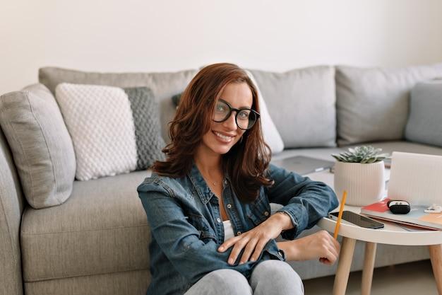 Europejska szczęśliwa urocza dama z kręconymi włosami siedzi w nowoczesnym biurze i pracuje