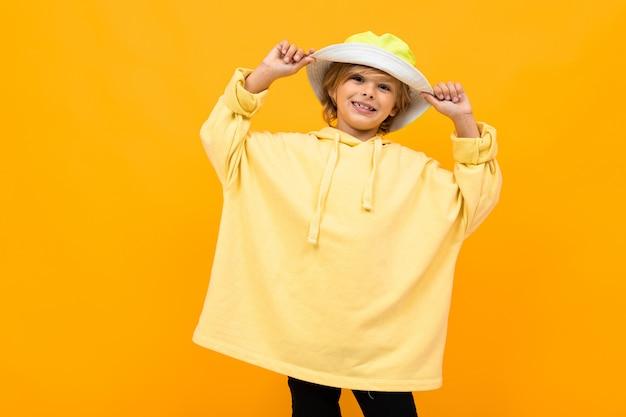 Europejski atrakcyjny chłopiec z panamą w lekkiej bluzie z kapturem na żółtej ścianie