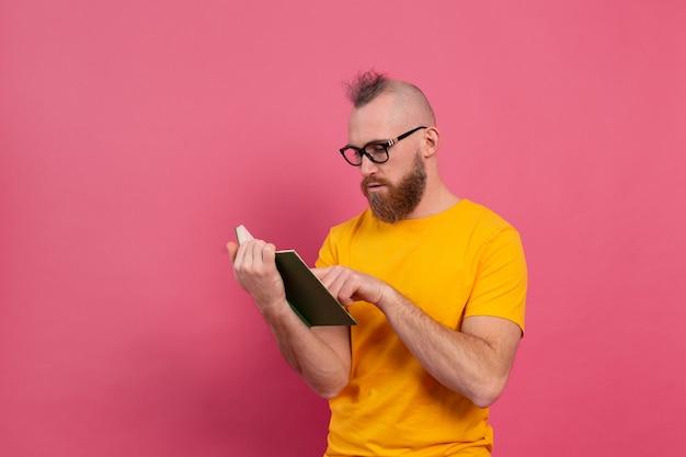 Europejski brodaty dorosły mężczyzna w okularach czytać książkę na różowym tle